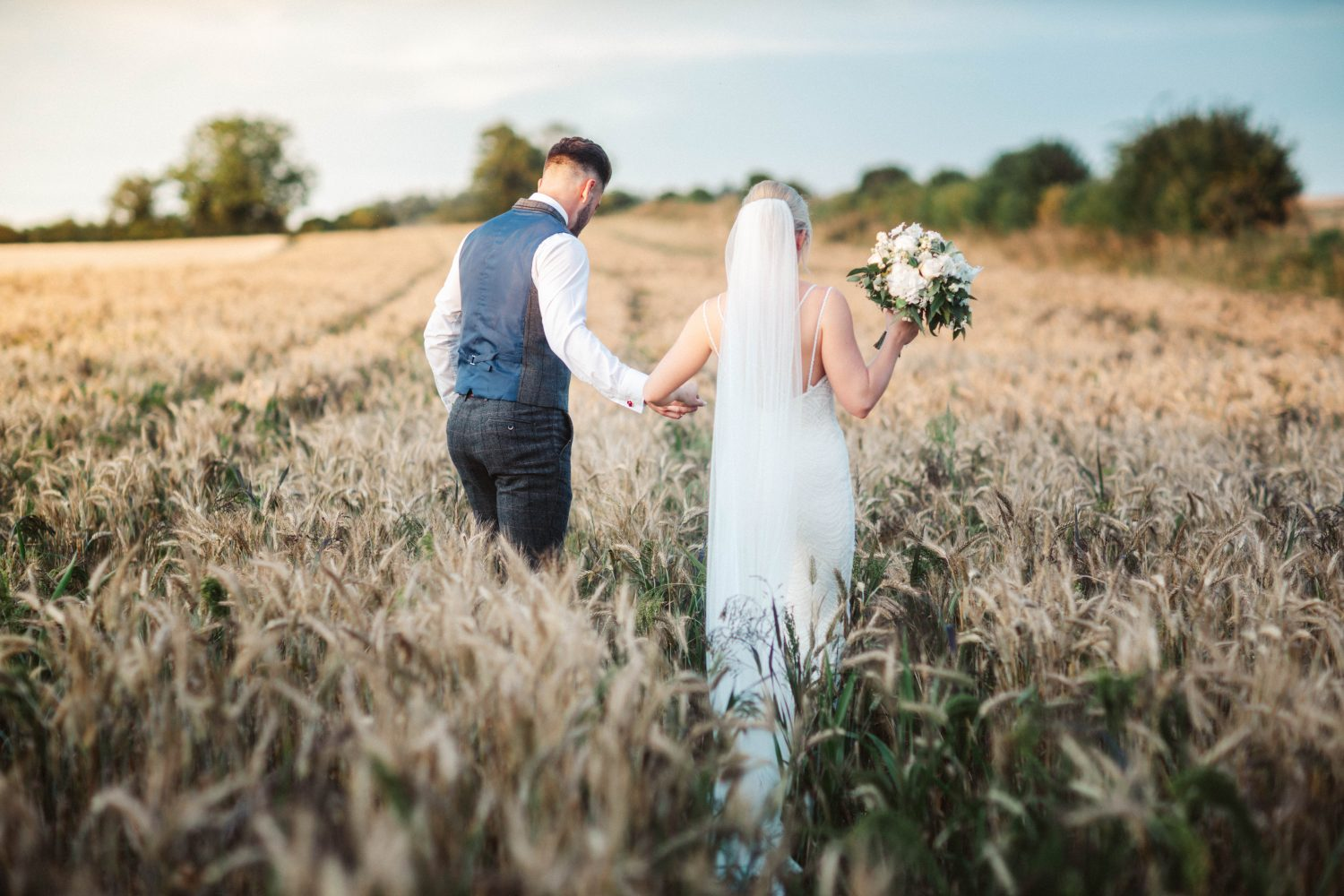Bride and groom walk in wheat field