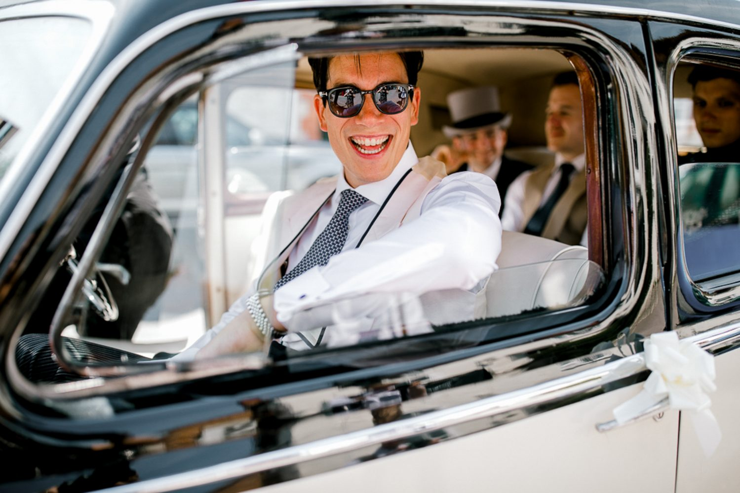 Groom laughing in wedding car