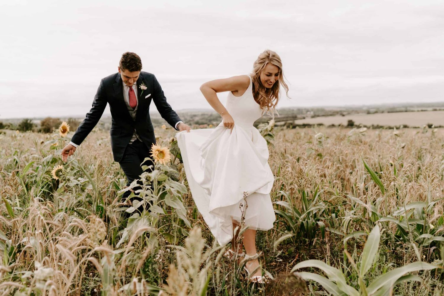 wedding couple walk through corn field